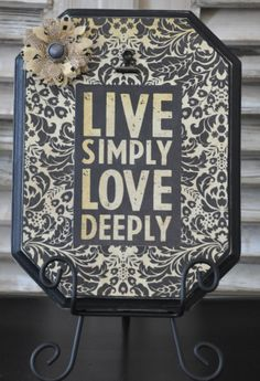 Black painted and distressed frame.  Embellished with 'Live Simply Love Deeply' and flower.  Will hold up to a 5x7 photo.