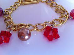 Bracciale color oro con perle rosse e bianche.
