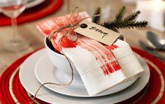 Detalle de una servilleta con estampado rojo y envuelta con cordel y una ramita, colocada sobre un bol en una mesa puesta.