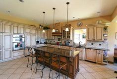 Mediterranean Kitchen with Kitchen island, Raised panel, Stone Tile, Pendant light, L-shaped, Custom hood, Flush, Glass panel