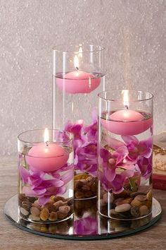 Set Of Three Lilac Floating Candles (£22) Set of 3 decorative glasses filled with lilac pebbles, artificial flowers and floating candles all on a mirrored base. Tallest glass is 20cm. Base diam. 20cm #floatingcandles