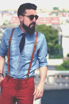 Shop this look on Lookastic:  http://lookastic.com/men/looks/red-chinos-and-blue-longsleeve-shirt-and-navy-tie-and-brown-suspenders/1123  — Red Chinos  — Blue Chambray Long Sleeve Shirt  — Navy Tie  — Brown Leather Suspenders