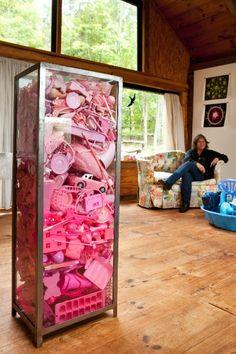 A artista plástica Portia Munson posa junto a uma de suas instalações, a vitrine repleta de objetos feitos de plástico rosa, e de uma banheirinha que contém outros elementos azuis (à dir.), que serão destinados a outra obra
