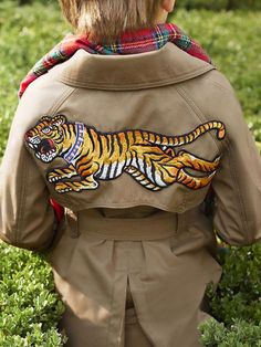 0153eec1638 A tiger appliqué embellishes the back of a double breasted trench from the  Gucci Children s Spring Summer 2017 collection.