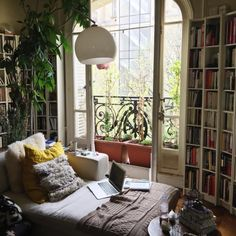 Tall windows, tall bookshelves, and tall plants are an incredible combo.