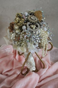 """Photo 2 of 2 • Vintage Brooch Wedding Bouquet. by Shannon Lee. • With a 50 cash outlay; I purchased 20 pieces of jewelry at Goodwill as well as a vintage christmas ornament and vintage ribbon. These items were used to create a lovely upscale Bridal Bouquet. I have found some of these selling for 400 and upwards. • This was created for the Goodwill 2013 Upcycled Contest. (previous photo is of the same Bouquet on burgundy (The Bouquet holder is actually the base for a """"Pillar Candle Holder"""")"""