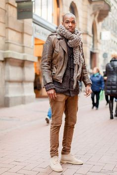 Shop this look on Lookastic:  https://lookastic.com/men/looks/biker-jacket-duffle-cardigan-chinos-desert-boots-scarf/4454  — Brown Knit Scarf  — Brown Leather Biker Jacket  — Brown Chinos  — Beige Suede Desert Boots  — Charcoal Duffle Cardigan