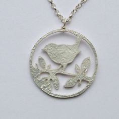 What better way to celebrate the beauty of birds than with this unusual sterling silver pendant. The bird and leaves have been delicately hand sawn within a circular shape to create a very unique design and finished with a reticulated surface texture. The pendant measures 25mm diameter and is finished with a sterling silver chain, available in a 16 inch or 18 inch length. Please specify when ordering. The bird outline shape is available as stud earrings and also as long drop earrings…