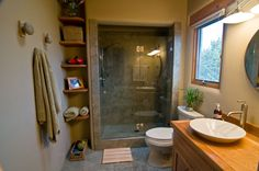 wood counter tops. White vessel sink. Glass shower doors. Large tile shower walls.