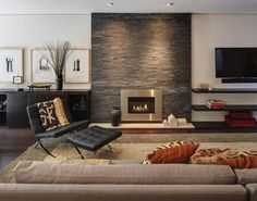 Contemporary Metro Living Room With Stainless Steel Fireplace Encased Stacked Stone Wall And Black Tufted Leather Barcelona Chairs Ottoman Beige Rug: Warm Elegance Interiors, Midvale Courtyard House