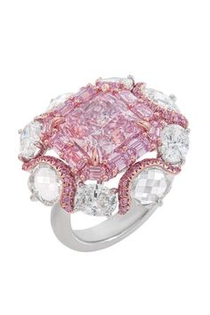 Ring features a magnificent 4.63 carat Fancy Purplish Pink centre diamond, within a border of Fancy Intense Purplish Pink emerald cut diamonds. Eight oval diamonds at the edges complete the distinct design. Soft curves weave together a beautiful border, crafting a sculptural composition that promises an eternal shine...