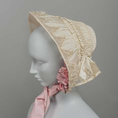 c. 1840.      White silk bonnet, trimmed with net and lace in zig-zag pattern around edges, with pink silk ribbons. H25.4 X W 30.5 X D 22.9
