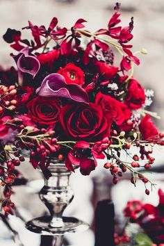Deep Reds & Purples: Red Roses, Purple Calla Lilies, Ranunculus, & Red Berries In A Silver Pedestal Bowl