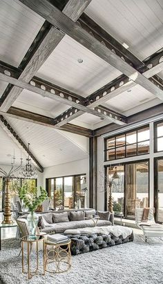 I really, really like this room and the mix of textures...gray wooden beams, lots of glass, beautiful fuzzy rug, velvet couch, gold and glass tables. All the elements work beautifully together.