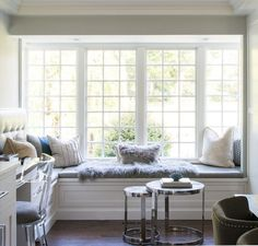 Stunning dining room boasts a white l-shaped window seat topped with a gray cushion accented with a gray sheepskin throw and an assortment of pillows.