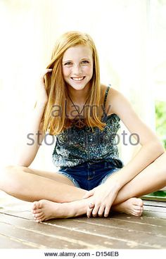 Smiling Young Woman Sits With Her Legs Crossed On A Wooden Floor. - Stock Image