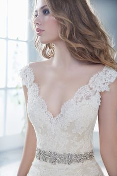 Ivory lace over wedding gown with V neckline by Alvina Valenta Bridal.
