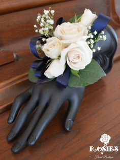 Corsage: includes white and light pink roses with gyp million star accents with a navy blue lace ribbon.
