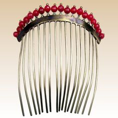 A classic Regency period gilded metal hair comb embellished with faceted faux coral beads CONDITION: good vintage condition SIZE: 4 ins h x 3½ ins w (10 x 9 cm) APPROXIMATE DATE: 1800s – 1830s