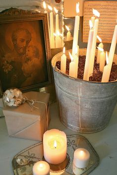 White candles in a galvanized bucket with coffee beans or gravel and sand, maybe?