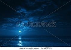 This photo illustration of a deep blue moonlit ocean at night with calm waves would make a great travel background for any coastal region or vacation. - stock photo