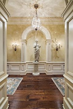Traditional Hallway with Chandelier, High ceiling, Hardwood floors, Wainscotting, Crown molding, Wall sconce
