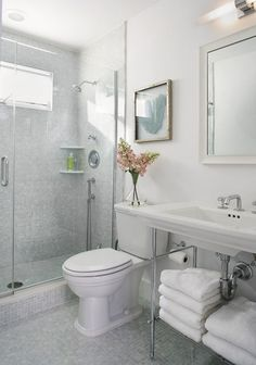 """""""The clear, frameless shower allows unobstructed views of the space,"""" says Rich. It also lets the natural light from the shower's window into the entire room. Using the same opalescent tile from the floor in the shower stall and up the wall creates continuity. These elements, plus using an open pedestal sink in lieu of a clunky vanity, make this bathroom look and feel much larger."""