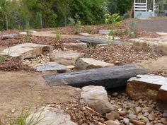 A very long dry creek bed with multiple railway sleeper bridges.