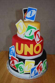 UNO Themed Cake for First Birthday - The first birthday theme was UNO.  It is a 3 tiered chocolate cake / chocolate mousse filling / chocolate frosting.  The cake is covered with fondant and the UNO cards are made of fondant.