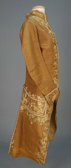 Coat, France, 1750-1775. Brown silk faille, decorated with net applique and polychrome silk floral, embroidered buttons, linen and silk lining.