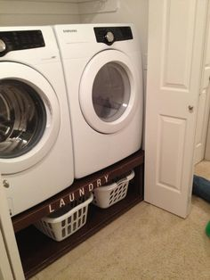 what a cool idea to raise the washer dryer to sensible heigh and store the laundry baskets underneath :)