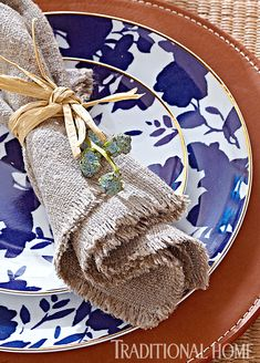 Stitched leather chargers provide a masculine base for gold-edged plates with a navy blue floral pattern.  Raffia and eucalyptus pods adorn a frayed napkin. - Photo: Peter Krumhardt / Design: Michelle Pulver
