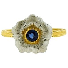 An 18k yellow and white gold ring set with a 3.6mm sapphire. Retail is $5890. DESIGNER: Buccellati MATERIAL: 18k Gold GEMSTONE: Sapphire DIMENSIONS: Ring Size 7, top measures 13mm x 12mm WEIGHT: 4 gra