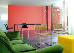 Modernité décontractée Dans cet espace très pur, la gamme de couleur tonique donne le ton actuel. Les propriétaires de ce salon ont mélangé avec beaucoup de décontraction l'orange légèrement désaturé du mur, le vert prairie du canapé et le jaune canari de la table basse. Le sol sombre en béton ciré, le mobilier noir ou en paille naturelle contrastent avec cet ensemble coloré.