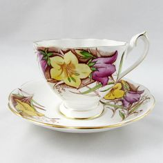Queen Anne tea cup and saucer feature large hand painted flowers. Tea cup and saucer have gold trimming. Queen Anne fine bone china tea cups and saucers were produced between 1911 and 1966 by Shore & Coggins. In excellent condition (see photos). Markings read: Queen Anne Fine Bone China