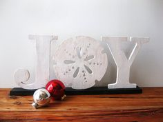 """Express the joy of the season and your love of the sea with this coastal version of a Christmas classic. The distressed white letters are mounted on a strip of pine that our artist painted black. She originally intended them to be 3 individual letters that you could hang on the wall or lean just, like our """"NOEL"""" listing. But I soon discovered that the pesky """"J"""" insists on tipping over if you try to lean it, and refuses to hang straight because of it's curved bottom and because all the weight…"""