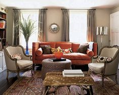 A 19th-century bull's-eye mirror hangs above a custom-made sofa by NL-GB in the living room; the Axis-deer ottoman is from Edwina Hunt, and the rug is a Turkish kilim.