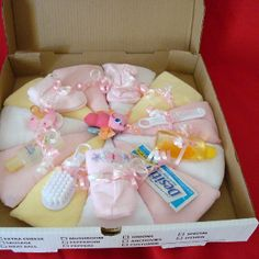 Fabulous Diaper Pizza   My diaper pizza has been the highlight of many a baby shower. The ingredients of this fabulous pizza are, 12 size Stage 1 Newborn Pampers. 12 baby washcloths, 1 pair of socks, 1 pacifier, Johnson & Johnson travel-size Desitin, and 1 cute, teething toy adorns the center. A sprinkle of curly ribbons tops it off.  My diaper pizza comes arranged on a cardboard base, sealed in shrink-wrap. The pizza box adds to the authenticity.