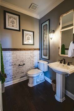 A brick accent wall, crown molding, and pedestal sink will make the powder room in your new home beautiful and unique. Seen in the Wheatland, a Grand Estates custom home. | Fischer Homes