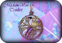 This pendant features a large genuine purple and brown agate, bronze colored copper wire, a lead-free owl charm, and genuine tanzanite Swarovski