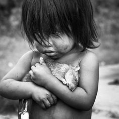 Menina guarani abraça firmemente um rato morto.
