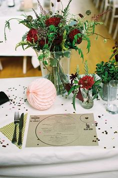 Quirky cool wedding decor with paper placemats and rustic style sprawling centrepieces using red flowers and ivy. Pink honeycomb paper balls decor. From: A Fashion Designer Bride And Her Childhood Sweetheart Groom | Love My Dress® UK Wedding Blog Film photography by http://www.ashtonjean-pierre.com/