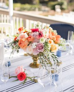 Twigg Botanicals used brass pedestal vessels of acacia, freesia, amaryllis, stock, spirea, roses, ranunculus, and ferns to anchorthe tables at this coastal wedding.