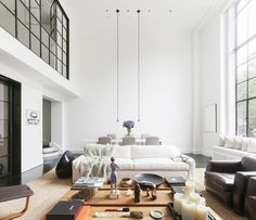 A spacious lofty living room with styled coffee table and white sofa