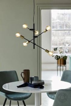 Brass detailing and soft shapes contrast with industrial bare bulbs, this pendant light features adjustable arms which can be rotated three-hundred and sixty degrees allowing you to customise your light source in whatever way imaginable. #Scandinavian #Nordic #Chandelier #Pendant #Kitchenlighting #Kitchenpendant #Diningpendant #Dining #Lightingdesign #Hanging #Lightingpendant #Interior #Decor #Scandinaviankitchen #Scandinavianinterior