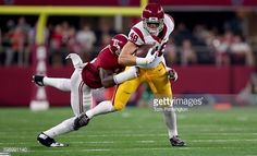 News Photo : Taylor McNamara of the USC Trojans is hit by...