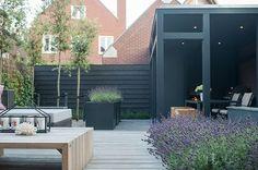 Kleine moderne tuin met veel plekken om te zitten