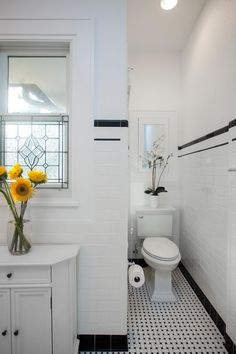 TriplePoint Design Build cleverly fashioned a small, out-of-the-way area to disguise the toilet for their Art Deco-style master bathroom redo. A medicine cabinet and a decorative flower arrangement in white complete the look.
