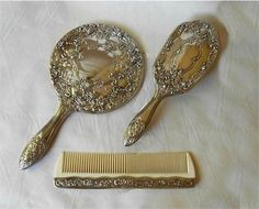 This is a gorgeous antique like 1980s vanity set of mirror, brush and comb. They appear to be silver plated but there are no marks at all. Perhaps nickel silver? Note that in pic 1 there is a LOT of reflections on the backs of the brush and mirror. These are not flaws!  Measurements:~ Mirror - 9 1/2 long - just the (glass)mirror itself is 4 1/4 diameter Brush - 8 long Comb - 7 1/4 long  I did some polishing and more can be done with a silver polish cloth. btw - the set is VERY ...