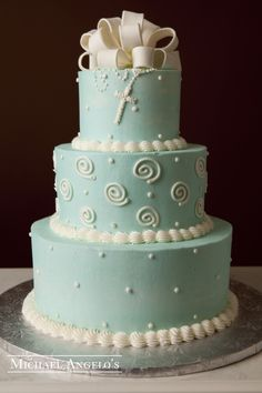 Baby Blue & Rosary #3Religious This design is made up of three-tiers iced in colored buttercream. Each layer is decorated with swirls and polka dots. The fondant bow or gum paste flowers make a great topper.  The rosary is made of buttercream.
